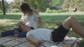 Το εφηβικό ζεύγος έχει το πικ-νίκ στο πάρκο απόθεμα βίντεο