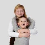 Το εφηβικό redhead κορίτσι αγκαλιάζει λίγο toothless χαμογελώντας αγόρι Στοκ εικόνες με δικαίωμα ελεύθερης χρήσης