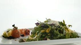 Το εύγευστος κόκκινος ψάρι ή ο σολομός κυλά με το πορτοκαλί χαβιάρι ζελατίνας και το πράσινο μίγμα σαλάτας στο πιάτο στο θολωμένο απόθεμα βίντεο