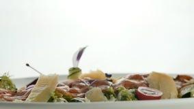 Το εύγευστος κόκκινος ψάρι ή ο σολομός κυλά με το πορτοκαλί χαβιάρι ζελατίνας και το πράσινο μίγμα σαλάτας στο πιάτο στο θολωμένο φιλμ μικρού μήκους