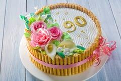 Το εύγευστο κέικ με τα τριαντάφυλλα, ο κρίνος, τα φύλλα και οι αριθμοί 90 έτη στον ανοικτό μπλε ξύλινο πίνακα κλείνουν επάνω με τ Στοκ εικόνες με δικαίωμα ελεύθερης χρήσης