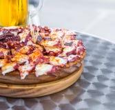 Το εύγευστο ξύλινο πιάτο του της Γαλικίας ύφους μαγείρεψε το χταπόδι και το ποτήρι της κρύας μπύρας gallega pulpo Λα Στοκ φωτογραφία με δικαίωμα ελεύθερης χρήσης