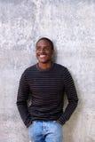 Το εύθυμο άτομο αφροαμερικάνων με παραδίδει τις τσέπες κοιτάζοντας μακριά Στοκ Εικόνες