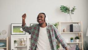 Το εύθυμο άτομο αφροαμερικάνων χορεύει και άκουσμα γέλιου τη μουσική με τα ακουστικά απολαμβάνοντας το ελεύθερο χρόνο στο σπίτι μ απόθεμα βίντεο