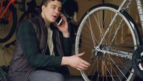Το εύθυμο άτομο συντήρησης μιλά στο κινητό τηλέφωνο εργαζόμενο στο εργαστήριο ποδηλάτων rapair ελέγχοντας τη ρόδα spokes και φιλμ μικρού μήκους