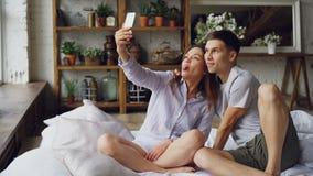 Το εύθυμο αγαπώντας ζεύγος παίρνει selfie με το smartphone που εξετάζει τη κάμερα, που θέτει και που κάνει τα αστεία πρόσωπα καθμ απόθεμα βίντεο