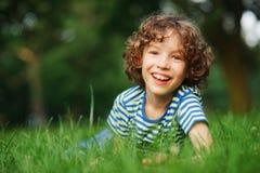 Το εύθυμο αγόρι βρίσκεται σε μια πυκνή πράσινη χλόη Στοκ εικόνα με δικαίωμα ελεύθερης χρήσης