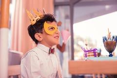 Το εύθυμο αγόρι που φορούν τη μάσκα και το έγγραφο στέφουν επισκεμμένος καρναβάλι στοκ εικόνες