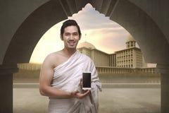 Το εύθυμο ασιατικό μουσουλμανικό άτομο με τα ενδύματα ihram παρουσιάζει κινητό τηλέφωνο Στοκ φωτογραφία με δικαίωμα ελεύθερης χρήσης