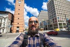 Το εύθυμο γενειοφόρο άτομο με ένα σακίδιο πλάτης κάνει selfie στο BA πόλεων Στοκ Εικόνες