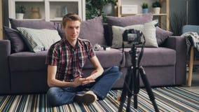 Το εύθυμο δημοφιλές vlogger νεαρών άνδρων καταγράφει το βίντεο για την ομιλούσα και gesturing εξέταση του σε απευθείας σύνδεση bl απόθεμα βίντεο