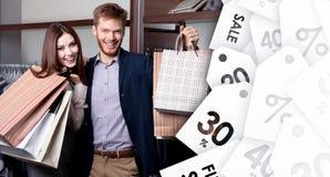 Το εύθυμο ζεύγος παρουσιάζει αγορές τους μετά από την πώληση στοκ φωτογραφία