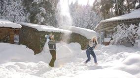 Το εύθυμο ζεύγος που έχει τη διασκέδαση υπαίθρια, νέα κορίτσια ρίχνει επάνω στο χιόνι Χειμερινή χαρά απόθεμα βίντεο