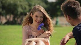 Το εύθυμο και γοητευτικό κορίτσι κάθεται σε έναν χορτοτάπητα και τις φλυαρίες με το φίλο της στην slo-Mo απόθεμα βίντεο