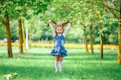 Το εύθυμο και ευτυχές μικρό κορίτσι με τα όπλα το καλοκαίρι σε ένα μπλε φόρεμα υπαίθρια σε ένα πάρκο χαμογελά γλυκά στοκ φωτογραφία