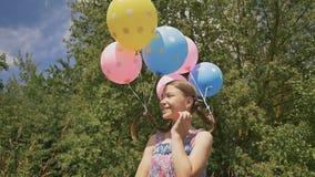 Το εύθυμο και όμορφο κορίτσι με τις ζωηρόχρωμες σφαίρες συνδέθηκε με την τρίχα και τις πλεξούδες της στο κεφάλι της Αστεία ιδέα μ απόθεμα βίντεο