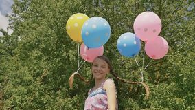 Το εύθυμο και όμορφο χαμόγελο κοριτσιών με τις ζωηρόχρωμες σφαίρες συνδέθηκε με την τρίχα και τις πλεξούδες της στο κεφάλι της Ασ απόθεμα βίντεο