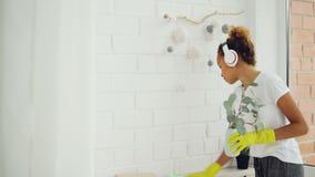 Το εύθυμο κορίτσι αφροαμερικάνων κοριτσιών κάνει τα οικιακά ξεσκονίζοντας χρησιμοποιώντας το ύφασμα και φορώντας τα γάντια, η νέα απόθεμα βίντεο
