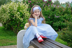 Το εύθυμο κορίτσι κάθεται σε έναν ξύλινο πάγκο στο πάρκο Στοκ Εικόνες