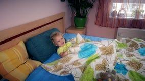 Το εύθυμο κορίτσι με τη σγουρή τρίχα έχει τη διασκέδαση κάτω από το περικάλυμμα στο κρεβάτι φιλμ μικρού μήκους