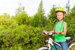 Το εύθυμο κορίτσι με τις πλεξούδες στο κράνος κρατά το ποδήλατο Στοκ εικόνες με δικαίωμα ελεύθερης χρήσης