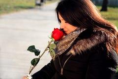 Το εύθυμο κορίτσι μυρίζει κόκκινο αυξήθηκε και απολαμβάνει Στοκ Εικόνες