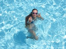 Το εύθυμο κορίτσι στη λίμνη που χαμογελά και που παρουσιάζει φυλλομετρεί επάνω στοκ φωτογραφίες