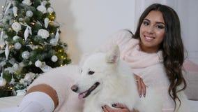 Το εύθυμο κορίτσι στο μακρύ πουλόβερ βρίσκεται στο πάτωμα κοντά στο άσπρο σκυλί στο υπόβαθρο του νέου δέντρου έτους φιλμ μικρού μήκους