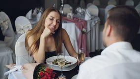 Το εύθυμο κορίτσι στο όμορφο φόρεμα μιλά στο φίλο της και γελά ενώ έχοντας το γεύμα μαζί στο εστιατόριο απόθεμα βίντεο