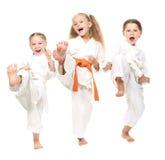 Το εύθυμο κορίτσι τρία έντυσε σε ένα άσπρο πόδι λακτίσματος κιμονό Στοκ εικόνες με δικαίωμα ελεύθερης χρήσης