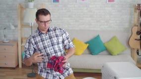 Το εύθυμο μέσης ηλικίας άτομο που ασχολείται με τις οικιακές μικροδουλειές πλένει τα πράγματα και χορεύει σε ένα σύγχρονο διαμέρι απόθεμα βίντεο