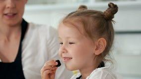 Το εύθυμο μικρό κορίτσι γλείφει ένα μούρο και την εξέταση τη κάμερα απόθεμα βίντεο