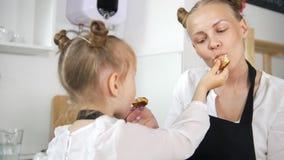 Το εύθυμο μικρό κορίτσι με τη μητέρα της ταΐζει σε μεταξύ τους τις σπιτικές τηγανίτες φιλμ μικρού μήκους