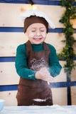 Το εύθυμο μικρό παιδί ψήνει τα κουλούρια αρτοποιός λίγα Γαλλικά κουλούρια φ στοκ φωτογραφίες