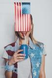 Το εύθυμο μοντέρνο κορίτσι στην αμερικανική πατριωτική σόδα κατανάλωσης εξαρτήσεων από μπορεί, με τη αμερικανική σημαία μπροστά α Στοκ φωτογραφία με δικαίωμα ελεύθερης χρήσης