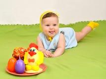 Το εύθυμο μωρό με μια ψυχαγωγία Πάσχας Στοκ Εικόνες