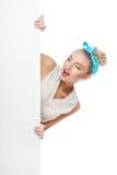 Το εύθυμο νέο κορίτσι κρύβει πίσω από το λευκό Στοκ Εικόνα