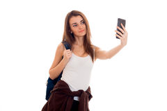 Το εύθυμο νέο κορίτσι σπουδαστών με το σακίδιο πλάτης κάνει selfie στο κινητό τηλέφωνό της που απομονώνεται στο άσπρο υπόβαθρο έτ Στοκ Εικόνες