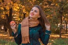 Το εύθυμο νέο κορίτσι στο πάρκο φθινοπώρου στο θερμό μαντίλι κρατά ότι η Apple στο χέρι του φαίνεται επάνω και χαμογελά Στοκ φωτογραφία με δικαίωμα ελεύθερης χρήσης
