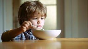 Το εύθυμο παιδί μωρών τρώει τα τρόφιμα τα ίδια με το κουτάλι Μικρό παιδί που έχει το πρόγευμα στην κουζίνα Το ευτυχές κουτάλι αγο απόθεμα βίντεο