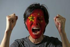 Το εύθυμο πορτρέτο ενός ατόμου με τη σημαία της Κίνας χρωμάτισε στο πρόσωπό του στο γκρίζο υπόβαθρο στοκ εικόνες