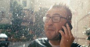 Το εύθυμο χαμογελώντας άτομο eyeglasses μιλά ευτυχώς μέσω του κινητού τηλεφώνου κατά τη διάρκεια της βροχής 4k μήκος σε πόδηα απόθεμα βίντεο