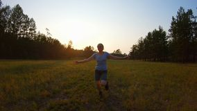 Το εύθυμο χαμογελώντας κορίτσι, οπλίζει το αυξημένο τρέξιμο πέρα από τον τομέα στο ηλιοβασίλεμα φιλμ μικρού μήκους