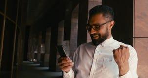 Το εύθυμο όμορφο αφρικανικό άτομο λαμβάνει τα sms με τις καλές ειδήσεις Έκφραση των συγκινήσεων 4K απόθεμα βίντεο