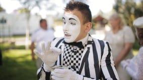 Το εύθυμο mime σε ένα ριγωτό κοστούμι κάνει έναν μορφασμό ενός καπνίζοντας προσώπου φιλμ μικρού μήκους