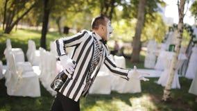 Το εύθυμο mime σε ένα ριγωτό κοστούμι κάνει ένα τρέχοντας άτομο παντομίματος απόθεμα βίντεο