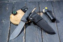 Το ελάχιστο σύνολο στρατιωτικού Ένα μαχαίρι, ένα paracord, μια πυξίδα και ένας φακός Στοκ Εικόνες