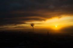 Το ελαφρύ ηλιοβασίλεμα ανατολής ουρανού ημέρας μοιρών ήλιων πόλεων σκιαγραφιών που χτίζει το βιομηχανικό ήλιο καλύπτει Στοκ εικόνες με δικαίωμα ελεύθερης χρήσης