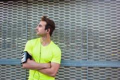 Το ελκυστικό άτομο απολαμβάνει ένα θαυμάσιο πρωί μετά από την έντονη ικανότητα εκπαιδευτικός ενώ ακούστε τη μουσική στα ακουστικά Στοκ Φωτογραφίες