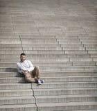 Το ελκυστικό άτομο με τη γενειάδα κάθεται στα βήματα Στοκ φωτογραφία με δικαίωμα ελεύθερης χρήσης